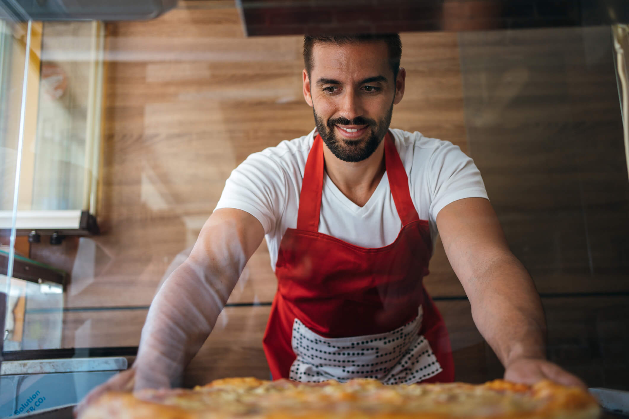 pizza maker putting pizza in display case