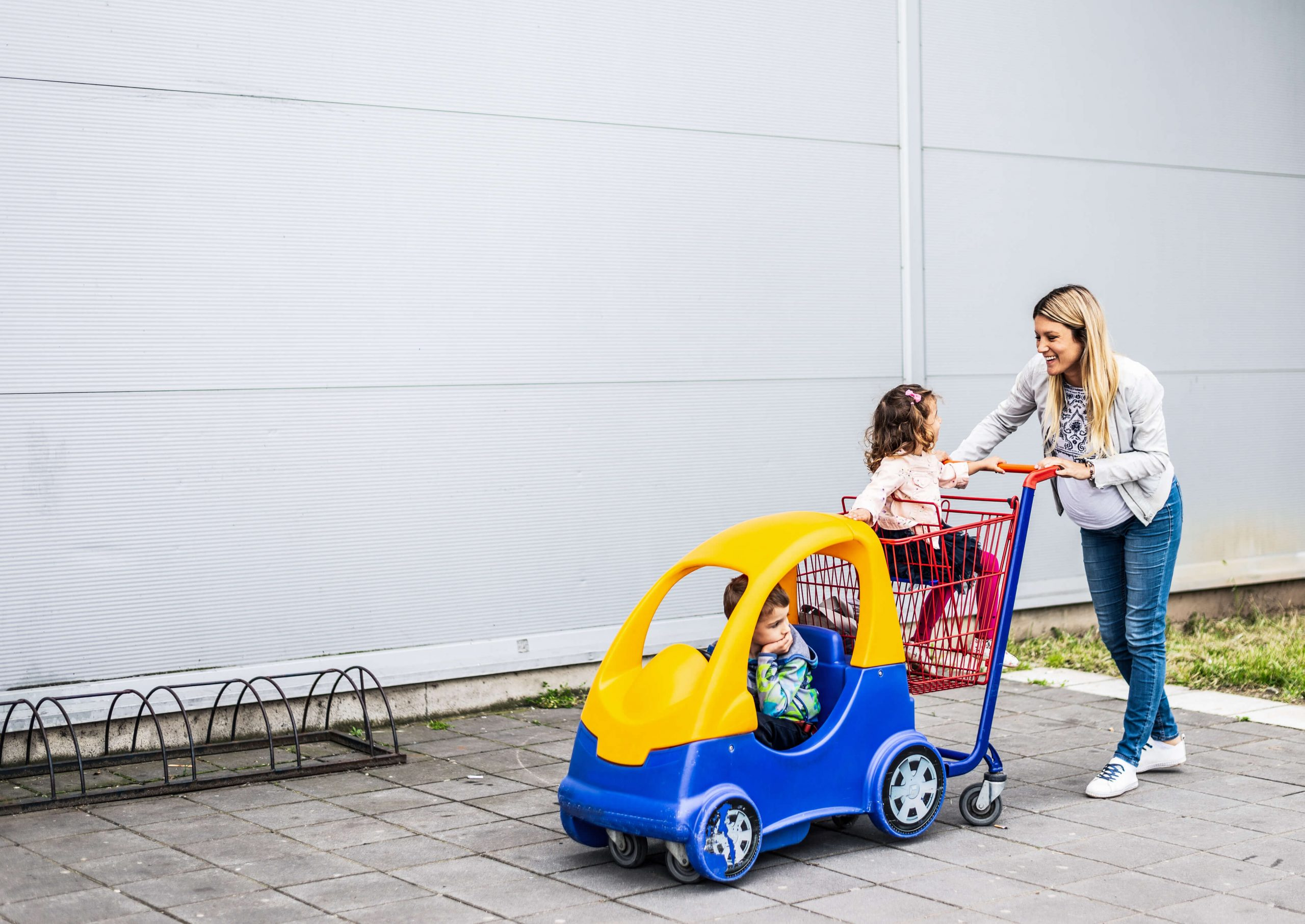 mother pushing her two children in a car themed grocery cart